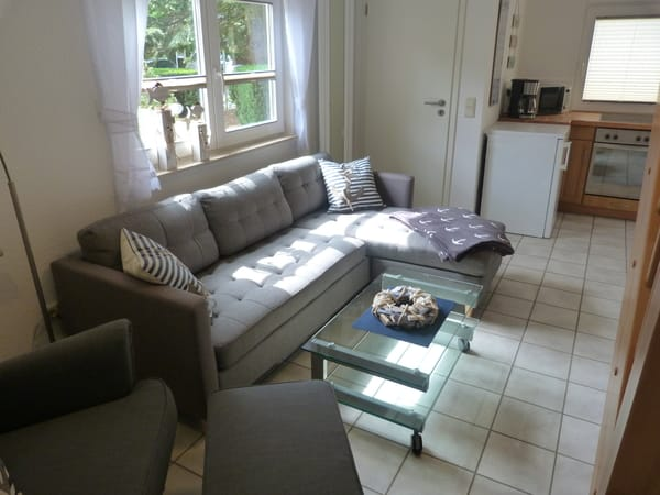 Das WZ ist mit einer Couch mit Récamiere und einem gemütlichen Ohrensessel mit Hocker und extra Leselampe ausgestattet.