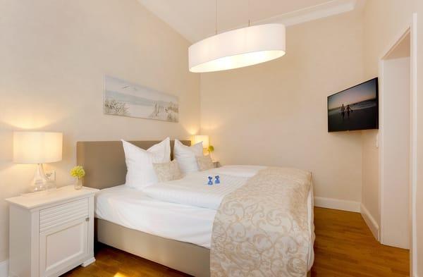 Die vier Schlafplätze verteilen sich auf das Schlafzimmer - mit einem bequemen und zugleich hochwertigem Boxspringbett.