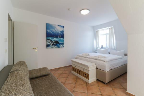 Schlafzimmer 2 mit Doppelbett, Ausziehcouch und Zugang zum Balkon