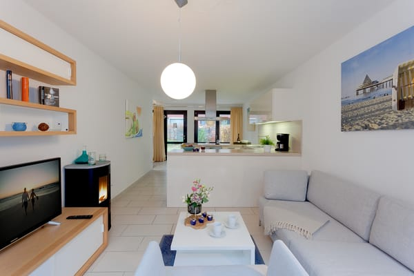 Modern und gemütlich zugleich – sowie Großzügigkeit auf ganzer Linie! Der stilvolle Wohnbereich verfügt über ein komfortables Sofa und einen Sessel.
