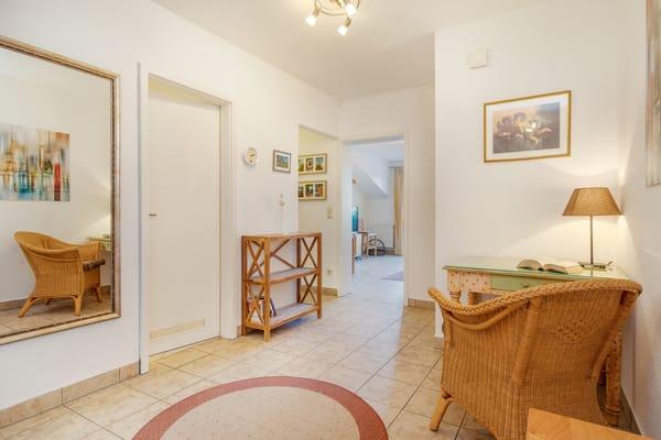 Blick vom Flur zur Badtür, zur Küchennische und zum Wohnzimmer.