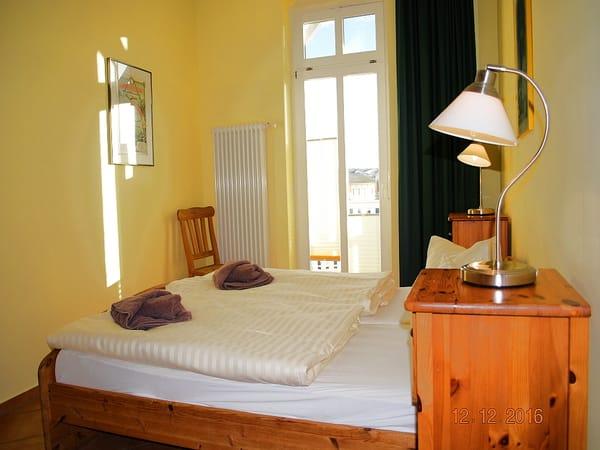 Blick in das Schlafzimmer mit Zugang zum Balkon