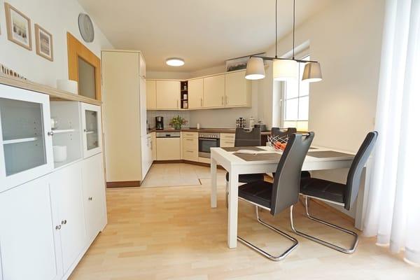 Wohnzimmer mit Esstisch und Küchenzeile