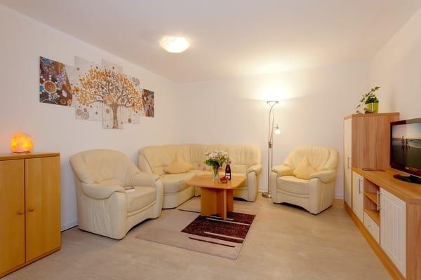 In dem großzügigen Wohnbereich wartet eine einladende Sitzecke mit Eckcouch und zwei Sesseln und Flat-TV ...
