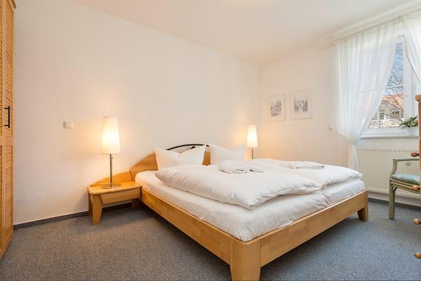 Das Schlafzimmer mit Doppelbett, Radio und Kleiderschrank.