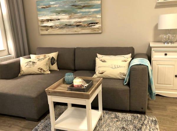 Wohnbereich ist mit einem gemütlichen Winkelsofa mit bequemen Rückenkissen und Ausziehfunktion (Liegefläche: 160 x 200 cm) ausgestattet