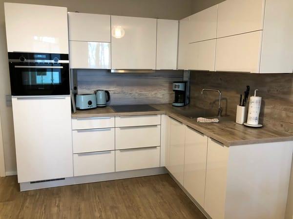 Die Küchenzeile ist mit Siemens-Elektrogeräten wie Induktionskochfeld, Backofen mit integrierter Mikrowelle, Kühlschrank mit Gefrierfach und Geschirrspülmaschine ausgestattet.