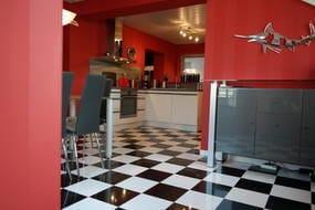 Blick auf hochwertige, neue Küche und Schachbrettfliesen