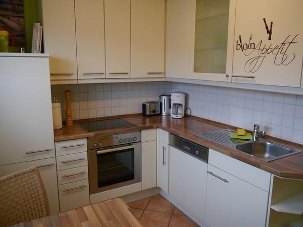 Einbauküche mit Ceranfeld und Geschirrspüler und kleinem Esstisch