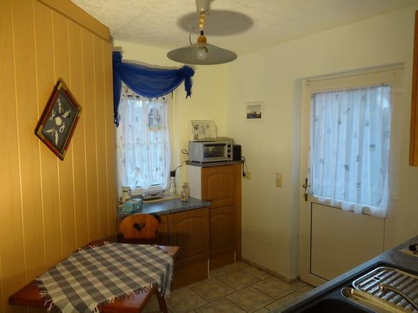 Kleine Küche mit Tisch und zwei Stühlen, Minibackofen, Toaster, Radio, ...