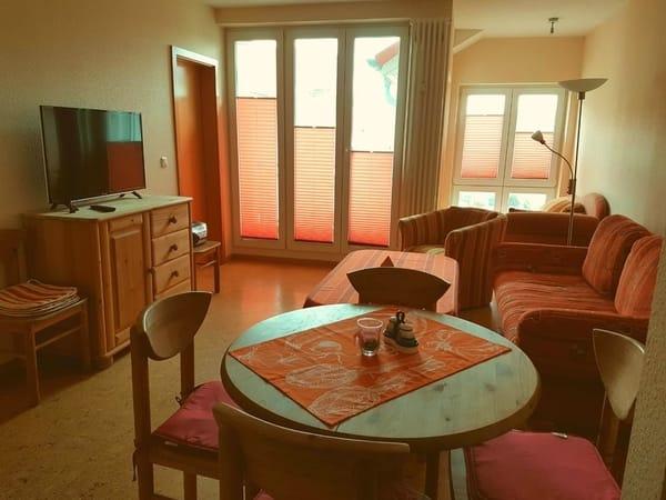 Blick Wohnzimmer Richtung Balkon mit großer Balkontür und wintergartenähnlichen Anbau mit Couch, Alle Fenster verfügen über hochwertige Plisees