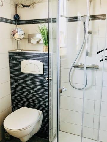Badezimmer mit Eckrunddusche und Fußbodenheizung