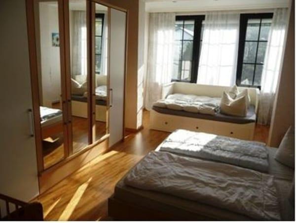 Großes Schlafzimmer mit Doppelbett, Kinderbettchen und Aufbettung im Erker