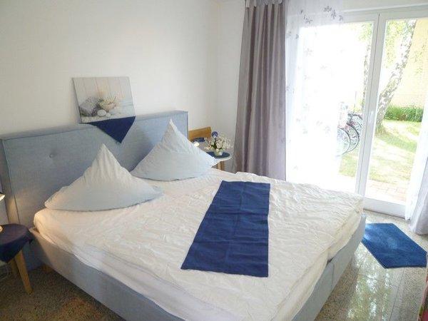 Modernes Schlafzimmer mit chicem blauen Bett, doppelflüglige Tür zur Terrasse