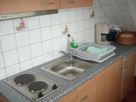....und helle Küchenzeile mit Herd,Abluft und Kühlschrank