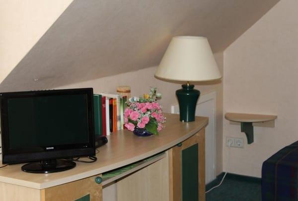 Der Flachbildschirm-TV befindet sich gegenüber der Sitzecke auf dem Schreibtisch und auch ein paar Bücher finden Sie hier