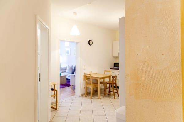 Sie stehen gerade im Flur und blicken durch die Küche in das Wohnzimmer.... Links geht es in das Bad, wo sich auch der Trockner und die Waschmaschine befindet.
