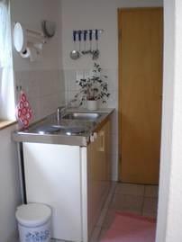 Eine Miniküche mit Kühlschrank, 2-Plattenkocher und Spüle