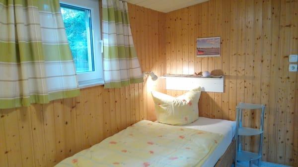 Im Schlafzimmer stehen die Betten hintereinander, ein Kleiderschrank ist im Zimmer