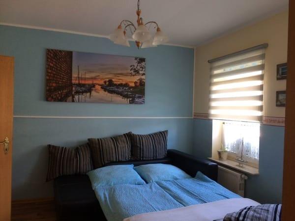 Wohn und Schlafraum der großen Ferienwohnung mit ausziehbarer Couch