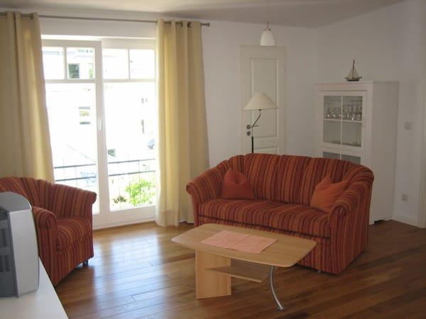 Wohnzimmer mit Sitzecke und Zugang zum Balkon
