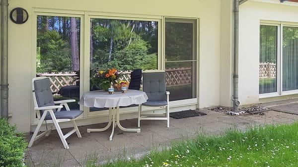 Terrasse mit Mobiliar, links vorm Wohnzimmer überdacht, rechts vorm Schlafzimmer