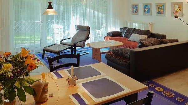 Wohnzimmer mit Sitzgruppe / Doppelbettcouch / Esstisch im Vordergrund
