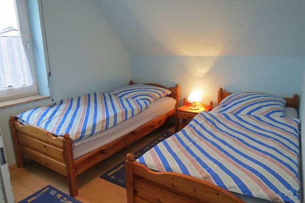 Das 2. Schlafzimmer im 1. Stk. hat 2 Einzelbetten, die 2 m lang sind.