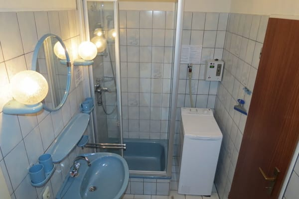 Das Bad mit Fenster befindet sich im Erdgeschoß. Sie sehen auch die Münzwaschmaschine. Eine Wäscheleine befindet sich im Garten.