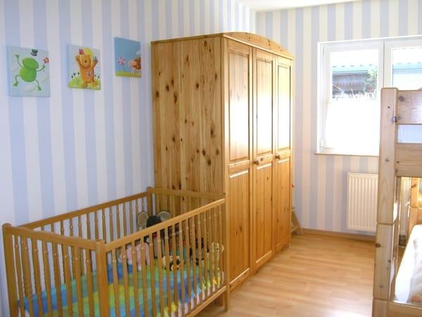 Kinderzimmer mit Etagenbett sowie Kinderbett und Hochstuhl