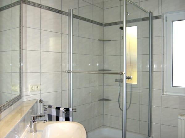 Bad mit Dusche und großem Spiegel