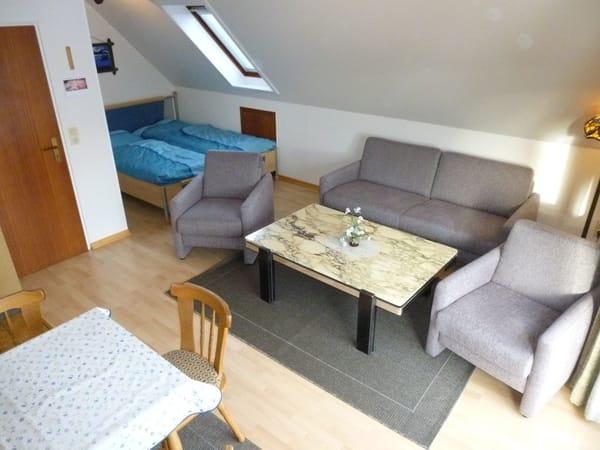 Sie sehen die Sofaecke. Hinten links sehen Sie das Doppelbett. Vorne ist der Eßtisch. Daneben befindet sich die Küchenzeile.