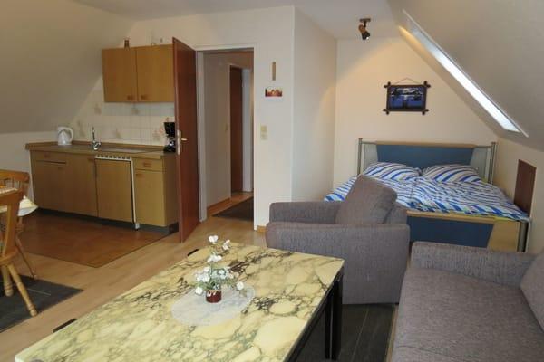 Das Wohnzimmer mit Küchenansicht.