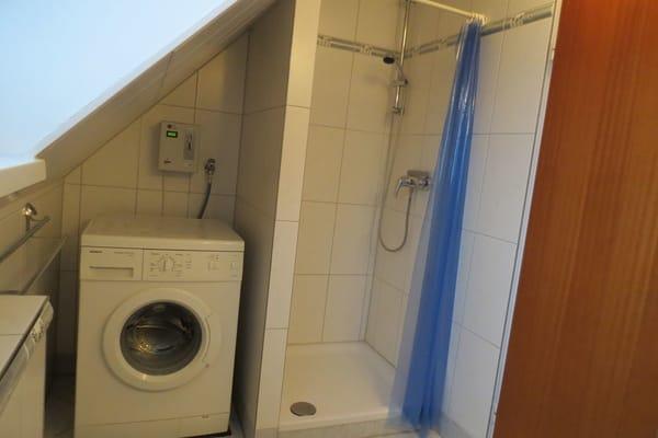 Duschbad mit Münzwaschmaschine, Wäscheleine befindet sich im Garten