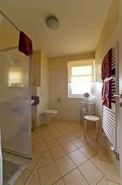 Badezimmer mit ebenerdiger Dusche, WC, Fußbodenheizung, Handtuchwärmer, Fön
