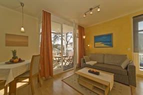 Wohnzimmer mit Ost- und Südbalkon (mit Blick zur Ostsee), Couch, Sessel, LCD-TV mit DVD-Player, Radio/CD-Stereoanlage, Internetzugang