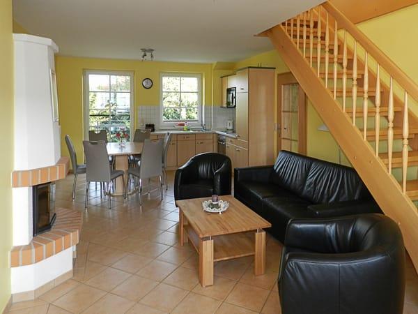Wohnzimmer mit Kamin und Küche