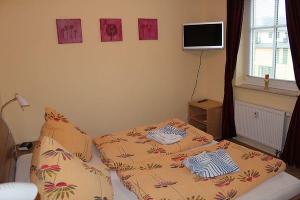 Das große Schlafzimmer mit einem 180x200cm-Doppelbett, Nachtschränken und Flachbildfernseher sowie DVD-Player...