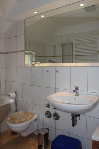 Das Badezimmer ist mit allem Notwendigen ausgestattet:  Waschbecken, WC, großem Spiegel mit Ablagefläche, Handtuchheizkörper, …
