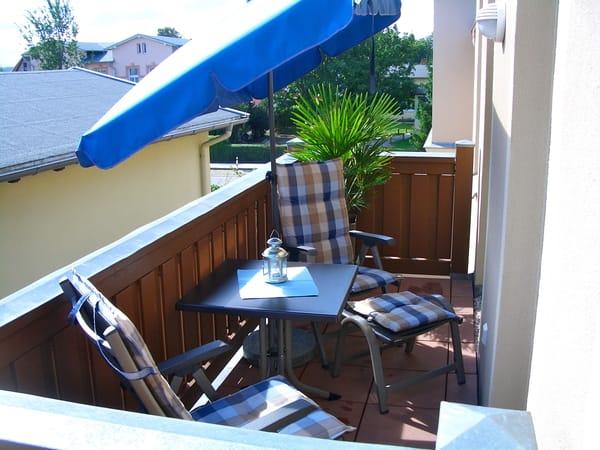 Der große Balkon mit gemütlichen Gartenmöbeln und Sonnenschirm