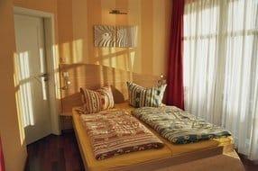 Schlafzimmer mit Doppelbett mit Balkonzugang