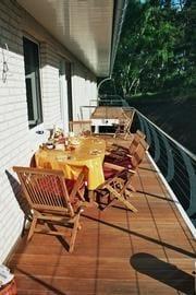 großer Balkon zur Gartenseite mit Sitzgelegenheit und Sonnenschirm