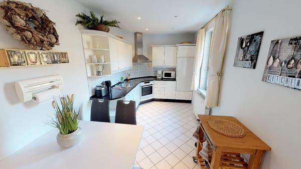 offene Wohnküche mit Essecke und Geschirrspüler, Herd, Microwelle, Toaster, Wasserkocher, Geschirr und alles was man in einer Küche erwartet