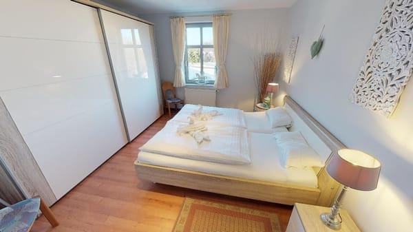 Teilansicht des Schlafzimmers mit großem Kleiderschrank bei Bedarf kann ein Kinderreisebett kostenlos zugestellt werden.