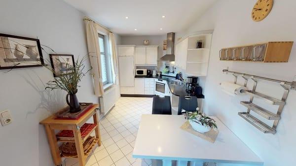 offene Wohnküche mit Geschirrspüler, Herd, Microwelle, Toaster, Wasserkocher, Geschirr und alles was man in einer Küche erwartet