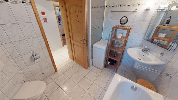 Badezimmer mit Badewanne und Waschmaschine und Duschkabine