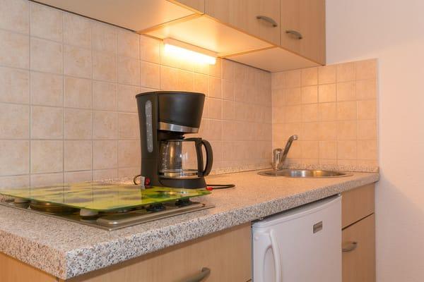 Küchenbereich mit Kühlschrank mit Gefrierfach und vielen weiteren Utensilien