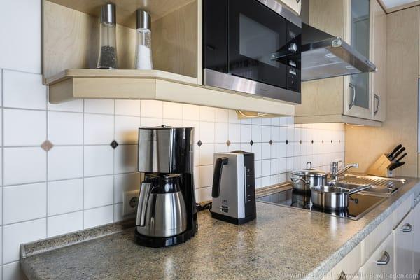 Küche mit Mikrowelle und Herd