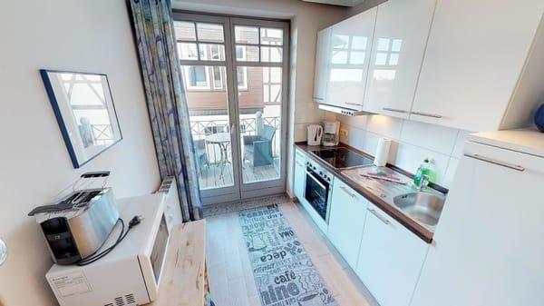 Die voll eingerichtete Küche der Wohnung Kuckuck, dahinter der Balkon, von dem aus Sie das Achterwasser sehen können.