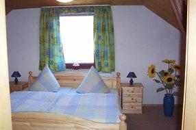 Schlafbereich mit Doppelbett Kleiderschrank und Komode